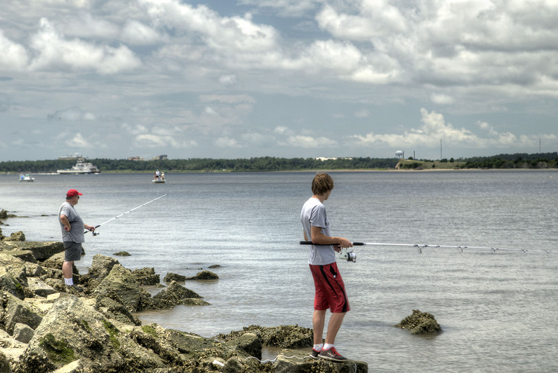 A father and son fish along The Rocks,  a seawall built in the late 1800s to prevent erosion into the Cape Fear River, at the Fort Fisher State Recreation Area on the southern tip of Pleasure Island in Kure Beach, NC on Saturday, July 12, 2014. Copyright 2014 Jason Barnette