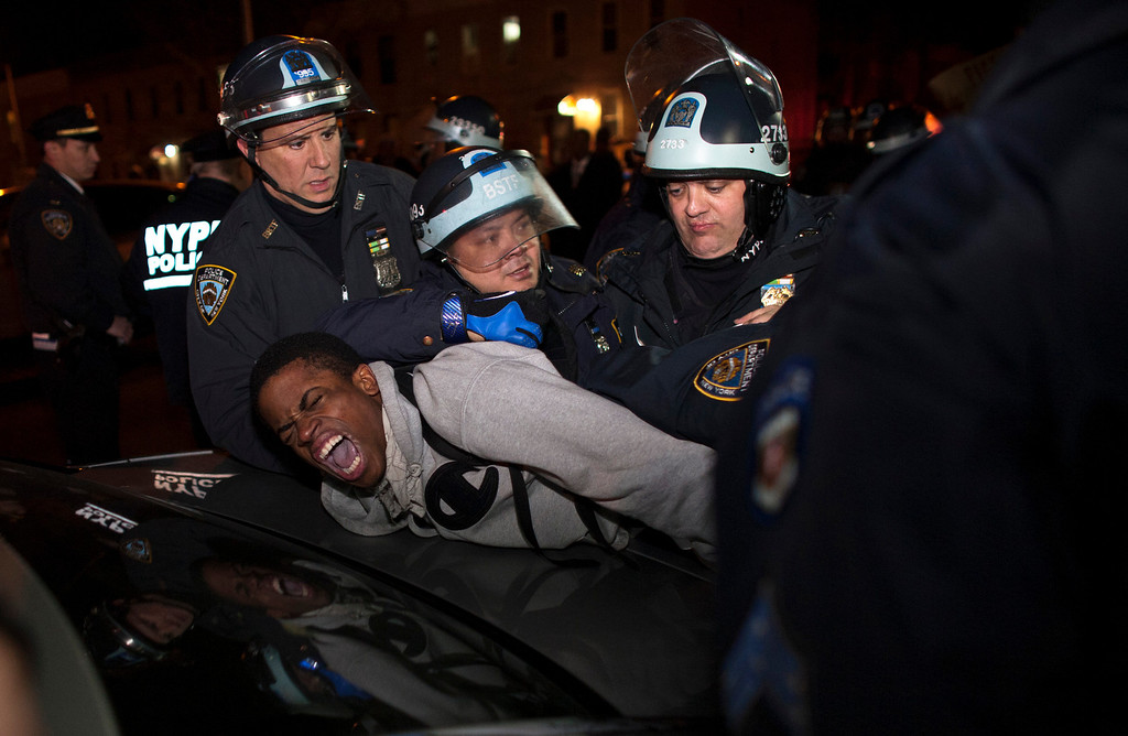 ". New York Police Department (NYPD) officers arrest a young man during a protest against the killing of 16-year-old Kimani ""Kiki\"" Gray who was killed in a shooting involving the NYPD, in the Brooklyn borough of New York March 13, 2013. REUTERS/Eduardo Munoz"
