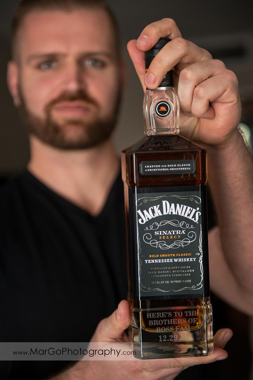 groom holding bottle of whiskey at San Diego Hyatt Regency Mission Bay Hotel