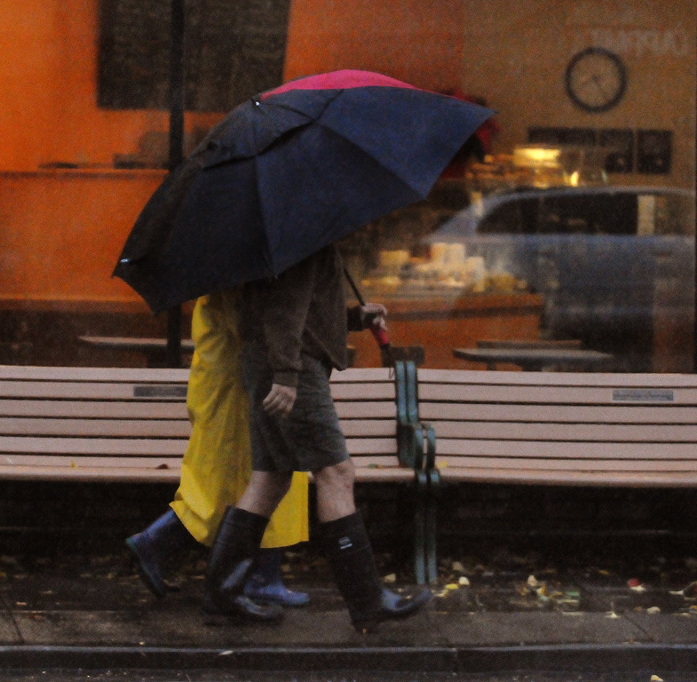 . Residents out in the rain in downtown San Anselmo on Thursday morning Dec. 11, 2014. (Robert Tong/Marin Independent Journal)