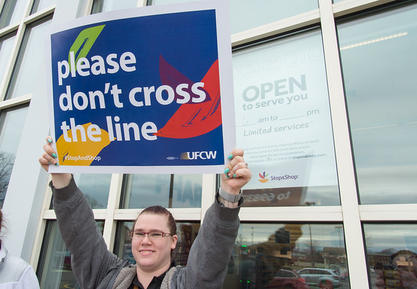 04/11/19 Wesley Bunnell | Staff Heather Johnson holds up her picket sign outside of the Stop & Shop in New Britain on Thursday afternoon as a company sign in the background advises would be customers of the limited hours and staff for the store.