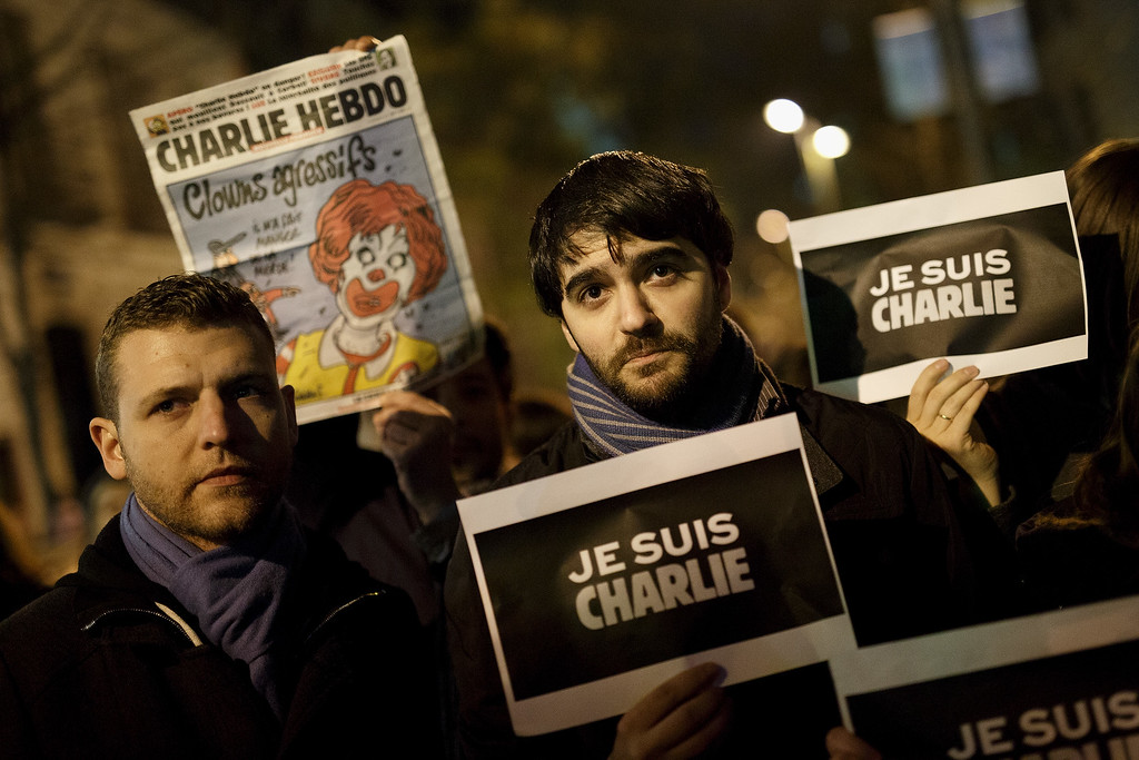 . MADRID, SPAIN - JANUARY 07:  People hold placards reading \'Je Suis Charli\' (I am Charlie) as another one holds a front page of \'Charlie Hebdo\' newspaper during a gathering of people showing their support for the victims of the terrorist attack at French magazine Charlie Hebdo, in front of the Embassy of France on January 7, 2015 in Madrid, Spain. Twelve people were killed, including two police officers, as two gunmen opened fire at the magazine offices of Charlie Hebdo in Paris, France.  (Photo by Pablo Blazquez Dominguez/Getty Images)