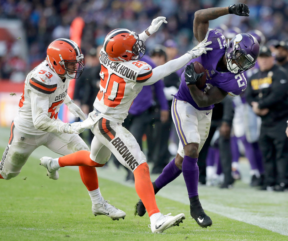 . Minnesota Vikings running back Jerick McKinnon, right, runs with the ball before being pushed out of bounds by Cleveland Browns safety Briean Boddy-Calhoun (20) as Browns linebacker Joe Schobert, left, watches during the second half of an NFL football game at Twickenham Stadium in London, Sunday Oct. 29, 2017. (AP Photo/Matt Dunham)