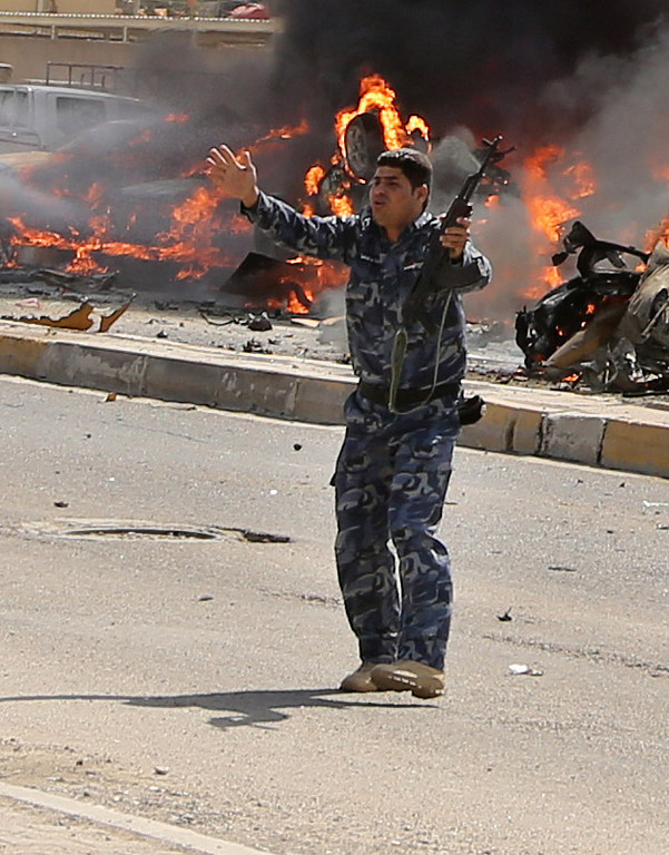 . An Iraqi policeman gestures near burning vehicles moments after one in a series of bombs hit the Shiite stronghold of Sadr City, in Baghdad, Iraq, Tuesday, May 13, 2014.  (AP Photo/Karim Kadim)