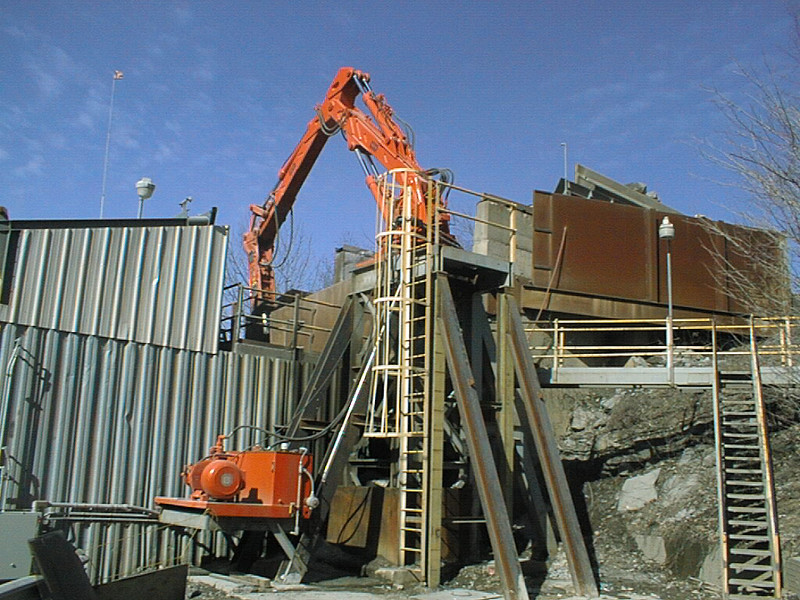NPK B700 pedestal boom system on platform breaking bridged rock at quarry.jpg