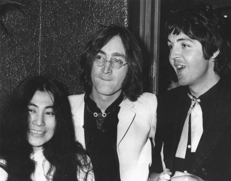 """. Beatles John Lennon, center, and Paul McCartney, arrive at the London Pavillion cinema on July 17, 1968 for the premiere of their new animation film \""""Yellow Submarine.\""""  At left is Japanese film producer Yoko Ono.  (AP Photo)"""