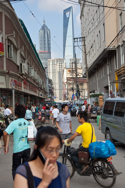 Shanghai, China - September 3, 2009: Busy Shanghai street in the foreground with two of  the tallest buildings in the world the Shanghai World Financial Center (left) and Jin Mao Tower (right) in the background. (Photo by: Christopher Herwig)