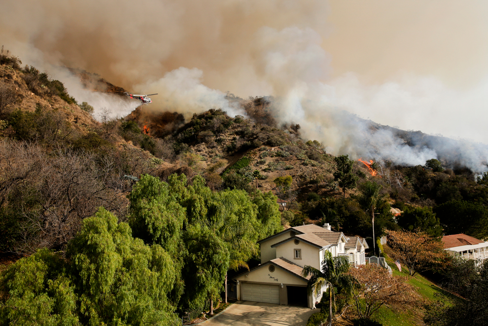 . A helicopter drops water on a fire burning near homes on Thursday, Jan. 16, 2014, in Azusa, Calif. A wildfire burned out of control near homes in the dangerously dry foothills of the San Gabriel Mountains early Thursday, fanned by gusty Santa Ana winds that spit embers into neighborhoods in the city below, igniting trees. Evacuations were ordered for houses at the edge of the fire. (AP Photo/Jae C. Hong)