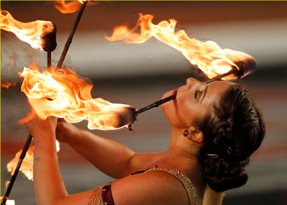 Description of . A Florida State Seminoles baton team member holds a flaming baton in her mouth as she twirls two others before her team plays against the Northern Illinois Huskies in the 2013 Discover Orange Bowl NCAA football game in Miami, Florida January 1, 2013. REUTERS/Andrew Innerarity