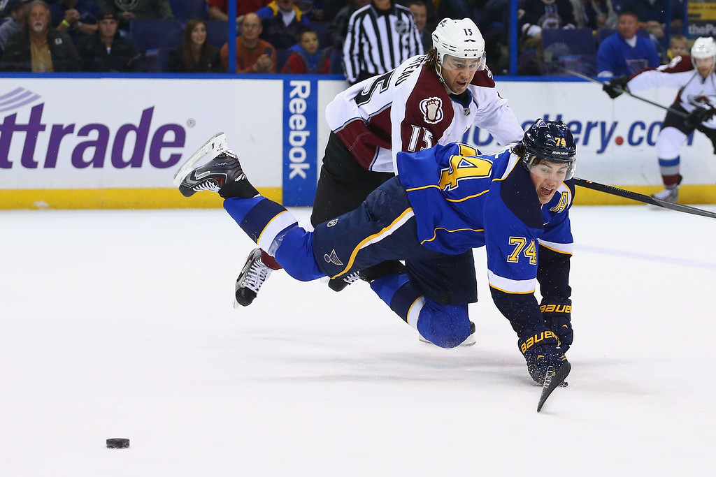 . ST. LOUIS, MO - NOVEMBER 14:  T.J. Oshie #74 of the St. Louis Blues is tripped up by P.A. Parenteau #15 of the Colorado Avalanche while pursuing a loose puck at the Scottrade Center on November 14, 2013 in St. Louis, Missouri.  (Photo by Dilip Vishwanat/Getty Images)