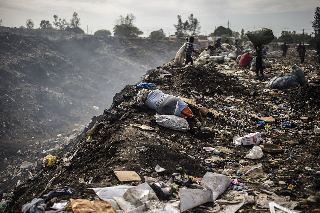 . A woman rests on the ground as rubbish pickers sift through garbage at the Maputo municipal garbage dumping site in Maputo on October 14, 2014. GIANLUIGI GUERCIA/AFP/Getty Images