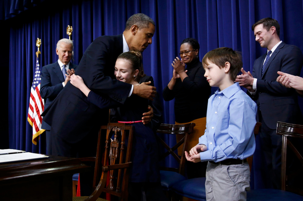 Description of . U.S. President Barack Obama  hugs 11-year-old Julia Stokes after unveiling a series of gun control proposals during an event at the White House in Washington, January 16, 2013. Julia was among a group of children who wrote the president letters about guns and gun control after the December 14 school shooting in Newtown, Connecticut, in which 20 children and six adults were killed   REUTERS/Jason Reed