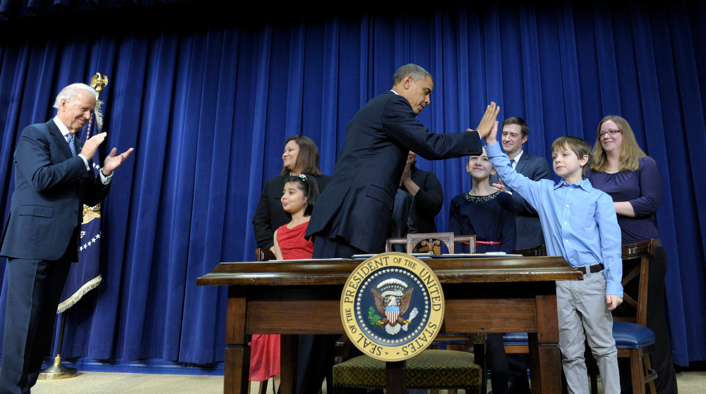 . President Barack Obama, accompanied by Vice President Joe Biden, left, gets a high-five from eight-year-old letter writer Grant Fritz during a news conference on proposals to reduce gun violence, Wednesday, Jan. 16, 2013, in the South Court Auditorium at the White House in Washington. Obama and Biden were joined by law enforcement officials, lawmakers and children who wrote the president about gun violence following the shooting at an elementary school in Newtown, Conn., last month. (AP Photo/Susan Walsh)