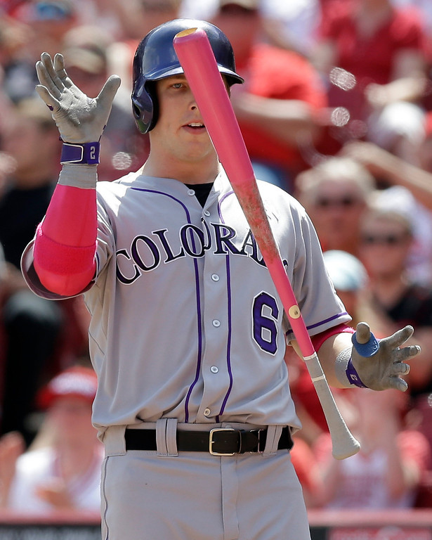 . Colorado Rockies\' Corey Dickerson strikes out against Cincinnati Reds relief pitcher Manny Parra in the eighth inning of a baseball game, Sunday, May 11, 2014, in Cincinnati. Cincinnati won 4-1. Dickerson was using a pink bat for Mothers Day. (AP Photo/Al Behrman)