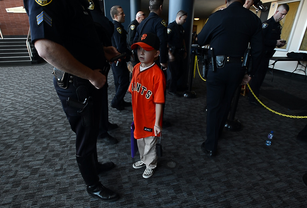. Johnny Schlemmer, 8, wears his Giants gear as he waits with father Richmond Police Sgt. Joey Schlemmer after being photographed with the World Series Trophy as it makes a stop at the Richmond Memorial Auditorium in Richmond, Calif. on Monday, Jan. 14, 2013.  (Kristopher Skinner/Staff)