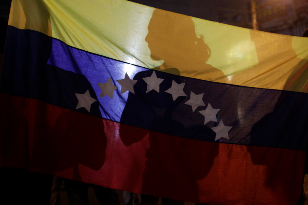 . Shadows are cast on a Venezuelan national flag during a protest supporting Venezuelan opposition leader Henrique Capriles in Panama City April 15, 2013. Capriles supporters protest by banging pots and pans on the streets of the city and outside the Venezuelan embassy on Monday after Capriles called for demonstrations to demand a recount of votes from Sunday\'s election to replace the late Hugo Chavez. Panama has one of the biggest Venezuelan community in Central America.  REUTERS/Carlos Jasso