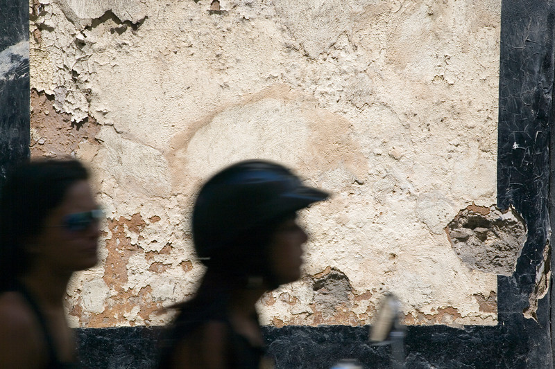 Graphic image of outlined, blurred riders against an old wall in Cadiz downtown.