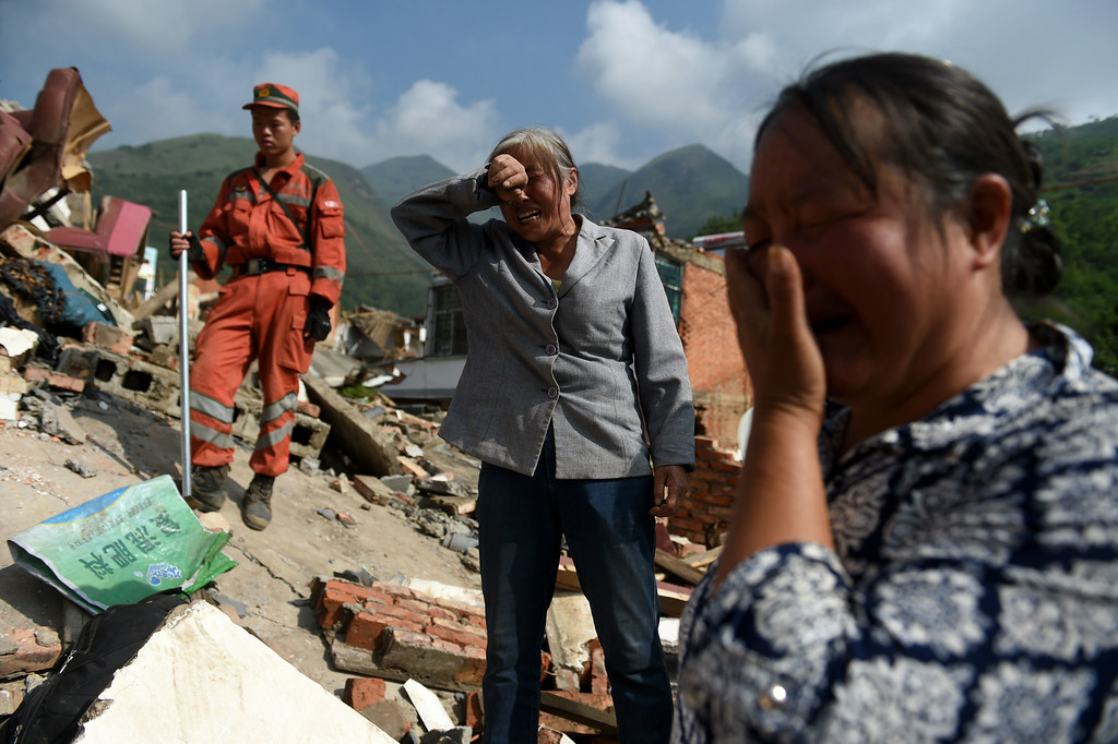 . Relatives of 71-year-old matriarch He Guixiu react as her body is found in a collapsed house at Longtoushan, in China\'s southwest Yunnan province on August 5, 2014.   AFP PHOTO/Greg BAKER/AFP/Getty Images