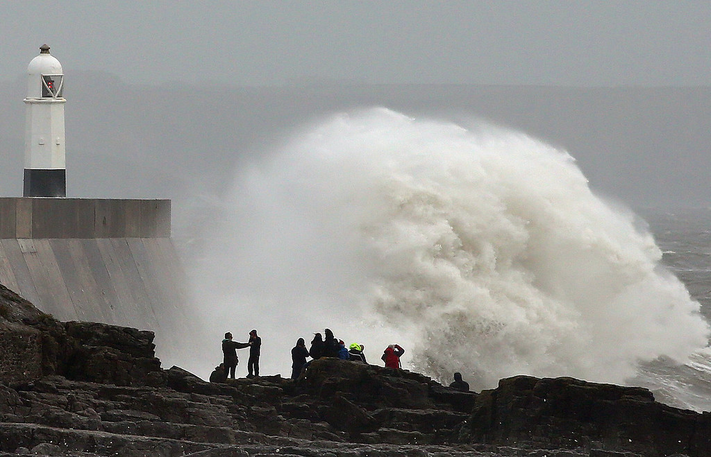 . People stand on the rocks as large waves break against barriers at the harbour in Porthcawl, south Wales on October 27, 2013 as a predicted storm starts to build. Britain was braced on October 27 for its worst storm in a decade, with heavy rain and winds of more than 80 miles (130 kilometres) an hour set to batter the south of the country.    GEOFF CADDICK/AFP/Getty Images