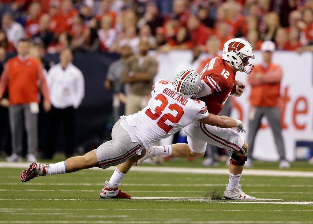 . Wisconsin quarterback Alex Hornibrook (12) runs with the ball as Ohio State linebacker Tuf Borland defends during the first half of the Big Ten championship NCAA college football game, Saturday, Dec. 2, 2017, in Indianapolis. (AP Photo/AJ Mast)