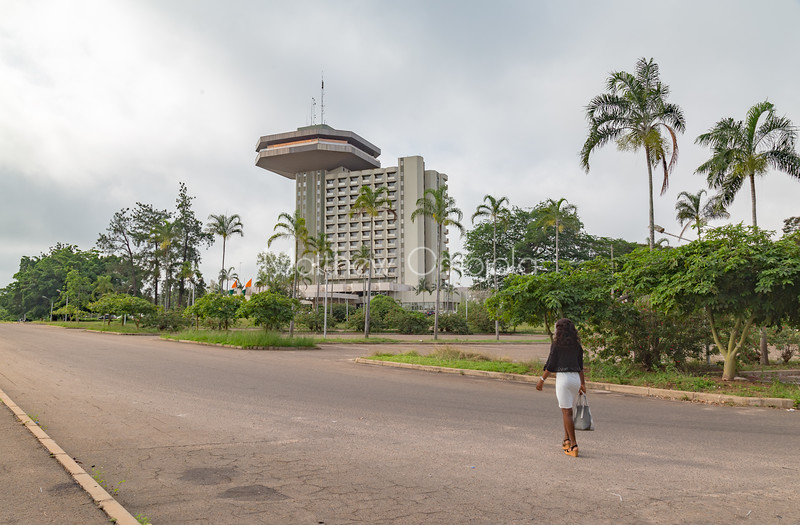 Young Ivorian lady walking to the President Hotel Yamoussoukro Ivory Coast Cote d'Ivoire. Beautiful garden.