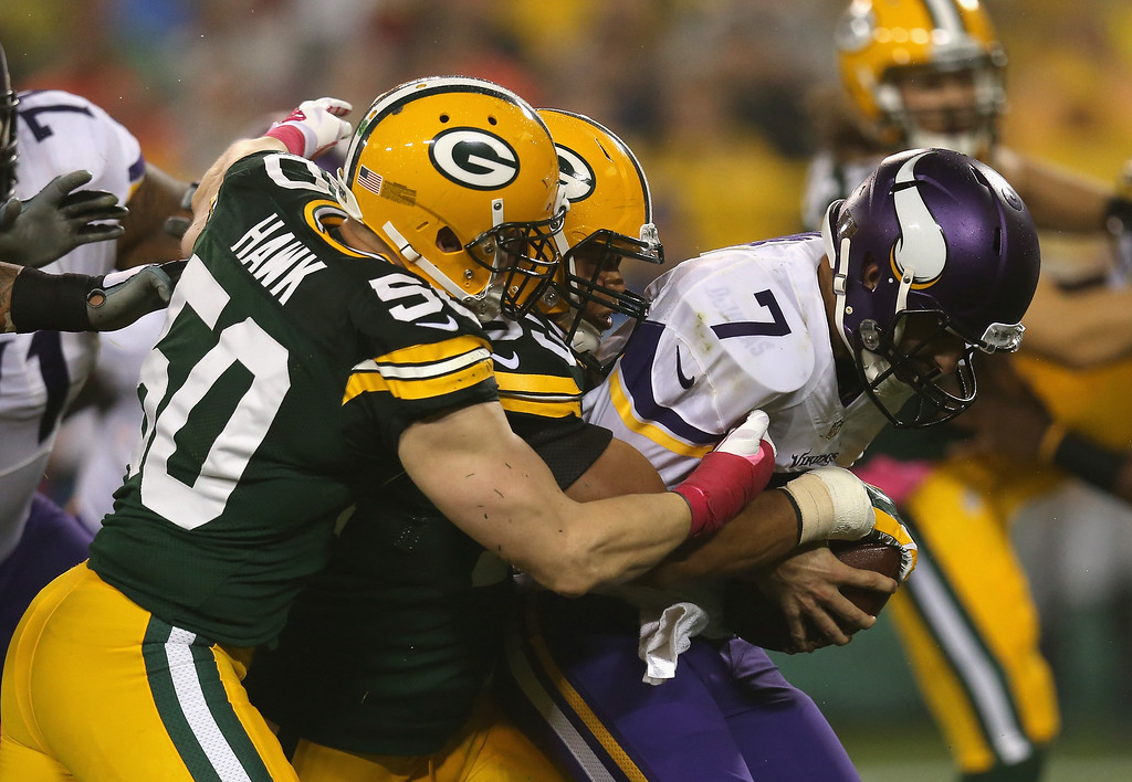 . GREEN BAY, WI - OCTOBER 02: Quarterback  Christian Ponder #7 of the Minnesota Vikings is sacked by  Nick Perry #53 and  A.J. Hawk #50 of the Green Bay Packers in the second quarter of the NFL game at Lambeau Field on October 2, 2014 in Green Bay, Wisconsin. (Photo by Jonathan Daniel/Getty Images)