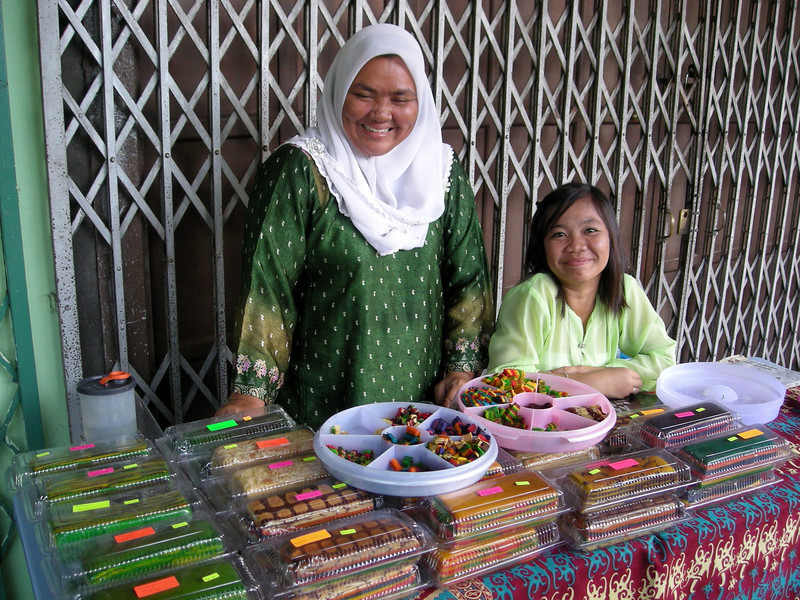 a Kak Lapis baker and her daughter with trays of different Kak samples at a sidewalk table in Kuching