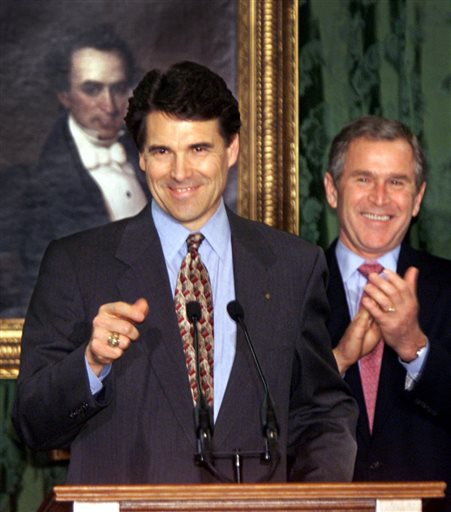 Description of . FILE - In this Dec. 21, 2000, file photo newly-sworn-in Governor of Texas Rick Perry acknowledges applause in the Senate Chamber of the Texas Capitol where he took the oath of office in the company of President-elect George W. Bush, who resigned as governor earlier in the day.  Behind them is a portrait of Texas pioneer Stephen F. Austin. Perry announced Monday, July 8, 2013, that he would not seek re-election as Texas governor next year. (AP Photo/J. Scott Applewhite, File)