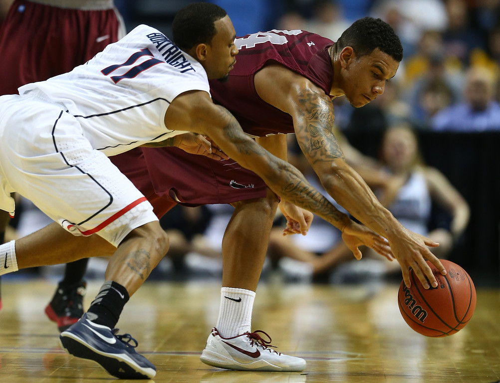 . BUFFALO, NY - MARCH 20: Chris Wilson #24 of the Saint Joseph\'s Hawks and Ryan Boatright #11 of the Connecticut Huskies battle for a loose ball during the second round of the 2014 NCAA Men\'s Basketball Tournament at the First Niagara Center on March 20, 2014 in Buffalo, New York.  (Photo by Elsa/Getty Images)