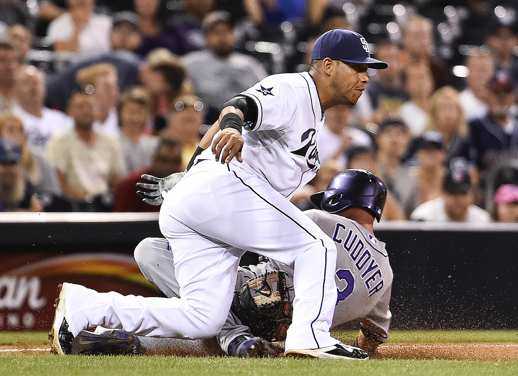 . SAN DIEGO, CA - SEPTEMBER 24:  Michael Cuddyer #3 of the Colorado Rockies slides into third base ahead of the throw to Yangervis Solarte #27 of the San Diego Padres during the eighth inning of a baseball game at Petco Park September, 24, 2014 in San Diego, California.  (Photo by Denis Poroy/Getty Images)
