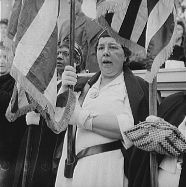 ". Arlington Cemetery, Arlington, Virginia. An American Legion color bearer singing \""America\"" in the amphitheater. Esther Bubley, Photographer.  Courtesy the Library of Congress"