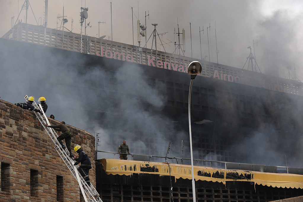 . Firemen climb a ladder as smoke billows from the terminal at the Jomo Kenyatta International Airport in Nairobi on August 7, 2013. A massive fire shut down Nairobi\'s international airport today with flights diverted to regional cities as firefighters battled to put out the blaze in east Africa\'s biggest transport hub.  AFP PHOTO / SIMON  MAINA/AFP/Getty Images