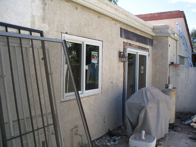 The kitchen window and sliding door in the side yard.