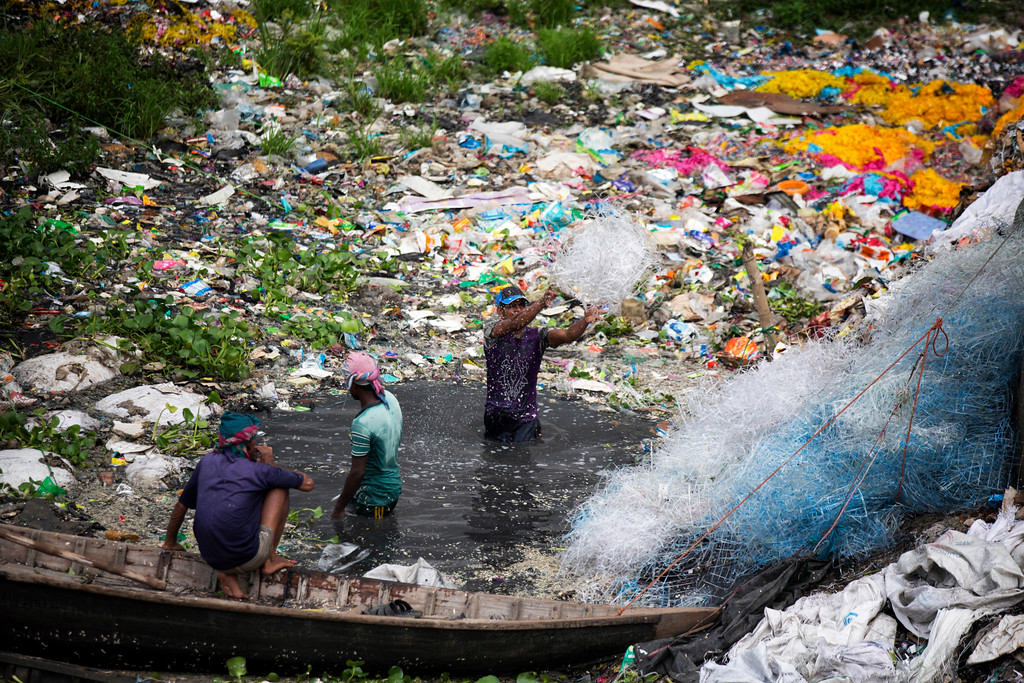 ". Bangladeshi men wash plastic strips in the river Buriganga in Dhaka, Bangladesh, Monday, June 4, 2018. The theme for this year\'s World Environment Day, marked on June 5, is ""Beat Plastic Pollution.\"" (AP Photo/A.M. Ahad)"