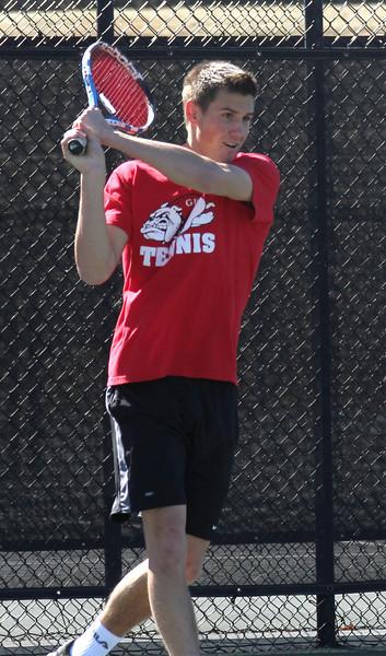 Julien Belair plays in a doubles match against the Trojans.