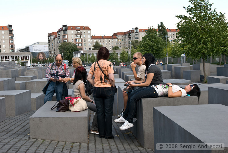 A group of tourists is resting in the Shoa memorial; the memorial is made up of 2,751 concrete blocks, emulating gravestones of varying heights; the memorial was completed in 2005