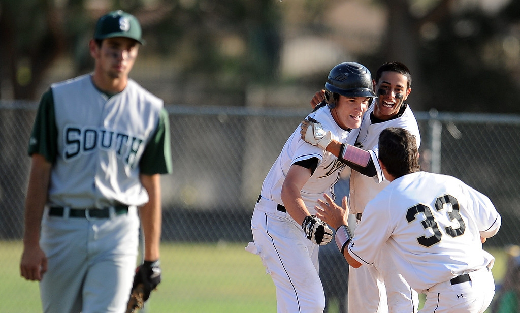 . Northview\'s Kollby Oriti is mobbed by teammate after walking with the bases loaded as teammate Alex Labor (not pictured) scores the winning run in the bottom of the seventh inning to defeat South (Torrance) 5-4 during a CIF-SS prep second round playoff baseball game against South (Torrance) at Northview High School on Tuesday, May 21, 2013 in Covina, Calif.   (Keith Birmingham Pasadena Star-News)
