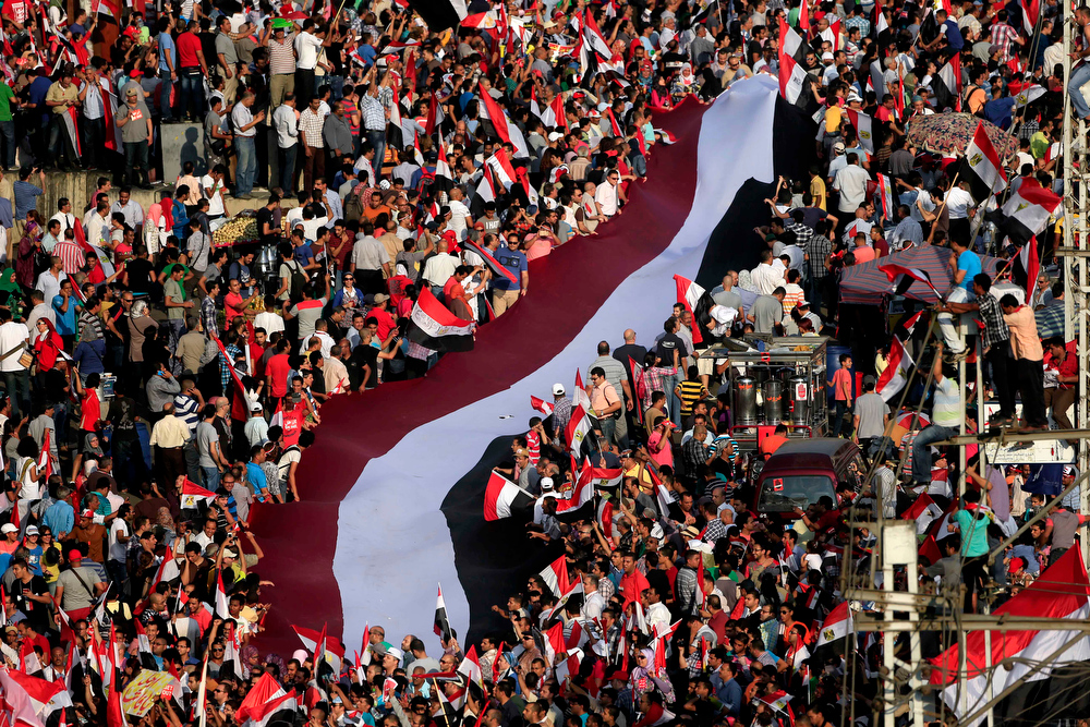 . Opponents of Islamist President Mohammed Morsi hold a large Egyptian national flag during outside of the presidential palace in Cairo, Egypt, Wednesday, July 3, 2013. The deadline on the military\'s ultimatum to President Mohammed Morsi has expired, with 48 hours passing since the time it was issued. Giant cheering crowds of Morsi\'s opponents have been gathered in Cairo\'s Tahrir Square and other locations nationwide, waving flags furiously in expection that the military will act to remove the Islamist president after the deadline ends.  (AP Photo/Hassan Ammar)