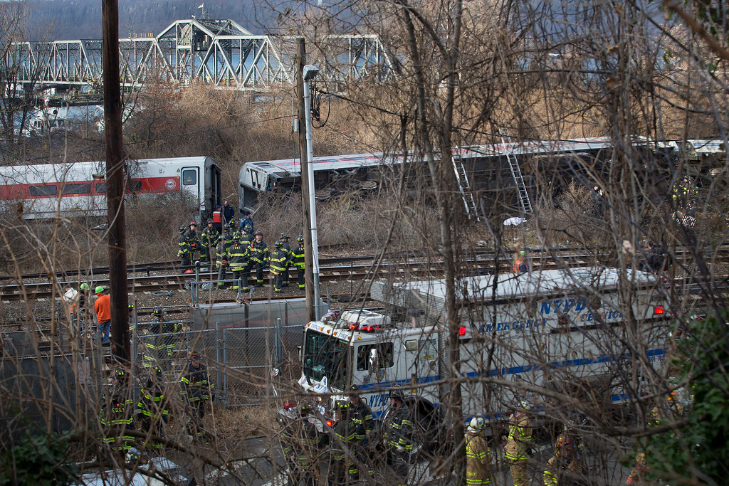 . First responders work the scene of a derailment of a Metro-North passenger train in the Bronx borough of New York Sunday, Dec. 1, 2013. The train derailed on a curved section of track in the Bronx on Sunday morning, coming to rest just inches from the water and causing multiple fatalities and dozens of injuries, authorities said. Metropolitan Transportation Authority police say the train derailed near the Spuyten Duyvil station. (AP Photo/John Minchillo)