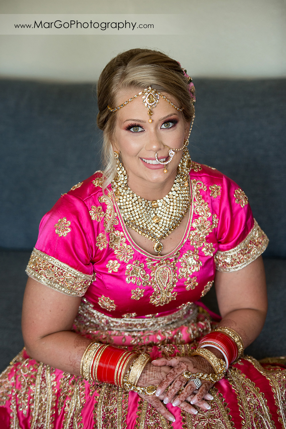 portrait of Indian bride in pink and golden dress wearing wedding jewelry