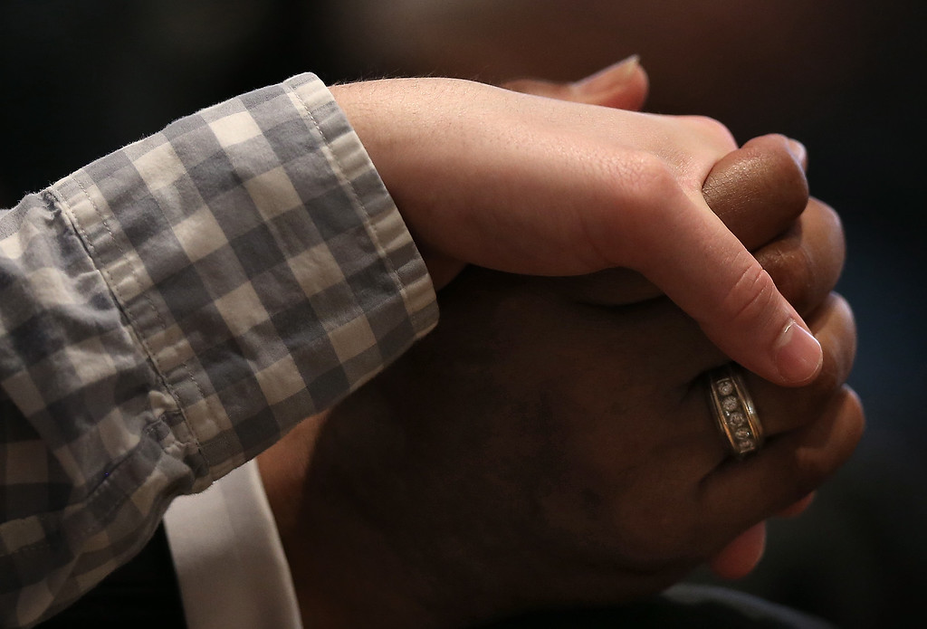 . Congregants hold hands during a prayer vigil for the nine victims killed at the Emanuel African Methodist Episcopal Church in Charleston, South Carolina at the the Metropolitan AME Church June 19, 2015 in Washington, DC. Earlier today the suspect in the case, Dylan Storm Roof, was charged with nine counts of murder.  (Photo by Win McNamee/Getty Images)
