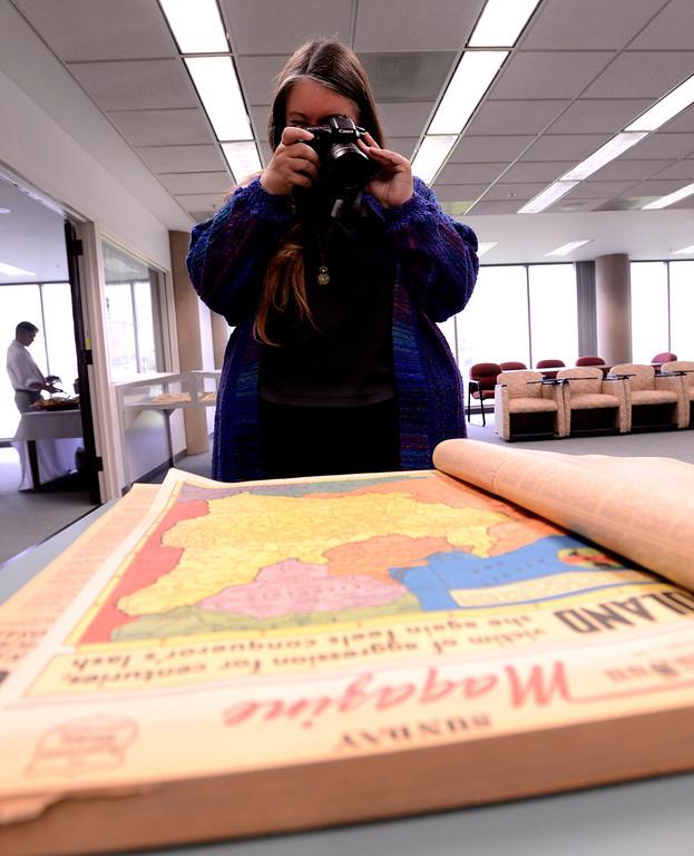 . Special Collections coordinator Jill Vassilakos-Long photographs a 1939 edition of The San Bernardino Daily Sun at California State University San Bernardino April 8, 2013.   GABRIEL LUIS ACOSTA/STAFF PHOTOGRAPHER.
