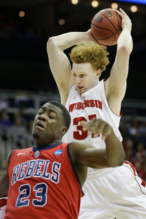 . Wisconsin forward Mike Bruesewitz (31) rebounds over Mississippi forward Reginald Buckner (23) during the first half of a second-round game in the NCAA college basketball tournament at the Sprint Center in Kansas City, Mo., Friday, March 22, 2013. (AP Photo/Orlin Wagner)
