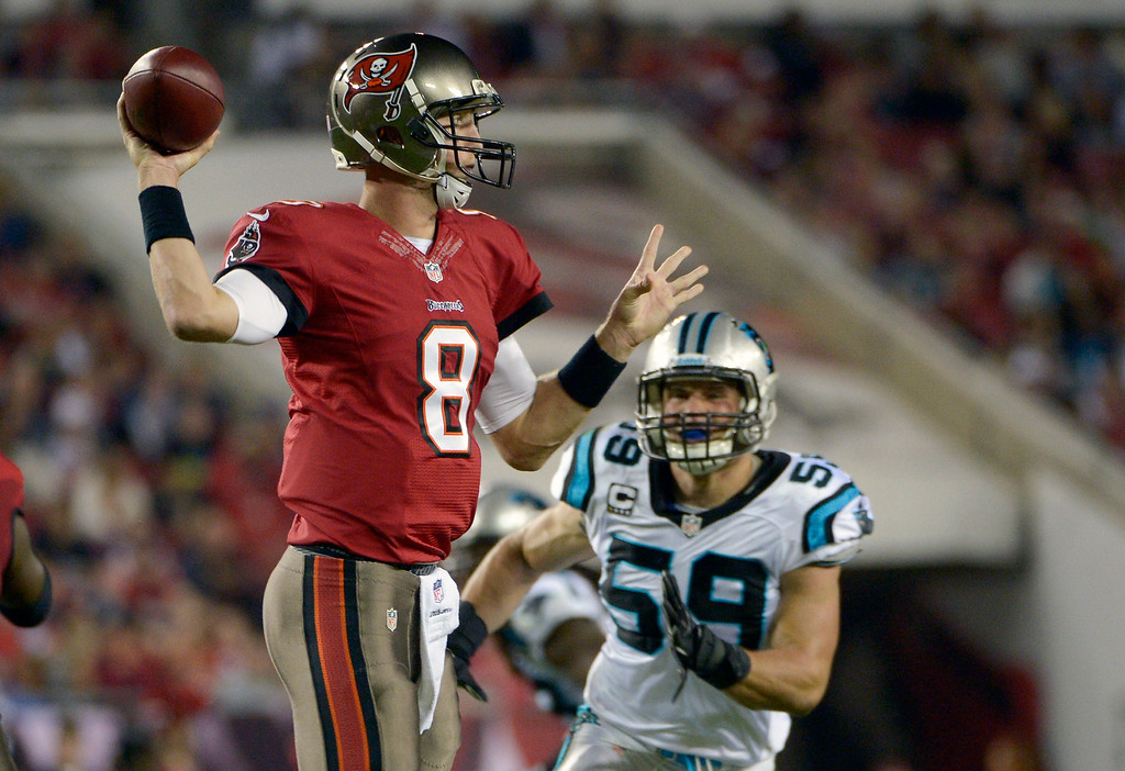 . Tampa Bay Buccaneers quarterback Mike Glennon (8) looks for a receiver as he is pressured by Carolina Panthers middle linebacker Luke Kuechly (59) during the first half of an NFL football game in Tampa, Fla., Thursday, Oct. 24, 2013. (AP Photo/Phelan M. Ebenhack)