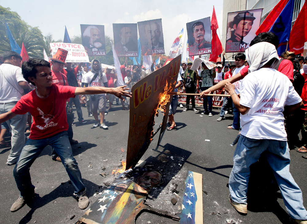 ". Protesters, mostly workers, burn a mural depicting U.S. President Barack Obama and Philippine President Benigno Aquino III after being blocked by police from getting closer to the U.S. Embassy in Manila to mark International Labor Day Wednesday May 1, 2013 in Manila, Philippines. The workers, who have demanding wage increases for years, assailed Aquino for his Labor Day ""gift\"" of non-wage benefits.  The protesters have been clamoring for years for a P125-Peso ($3.125) across-the-board wage hike and condemn the Government\'s policy of outsourcing labor which allegedly eliminates job security. (AP Photo/Bullit Marquez)"