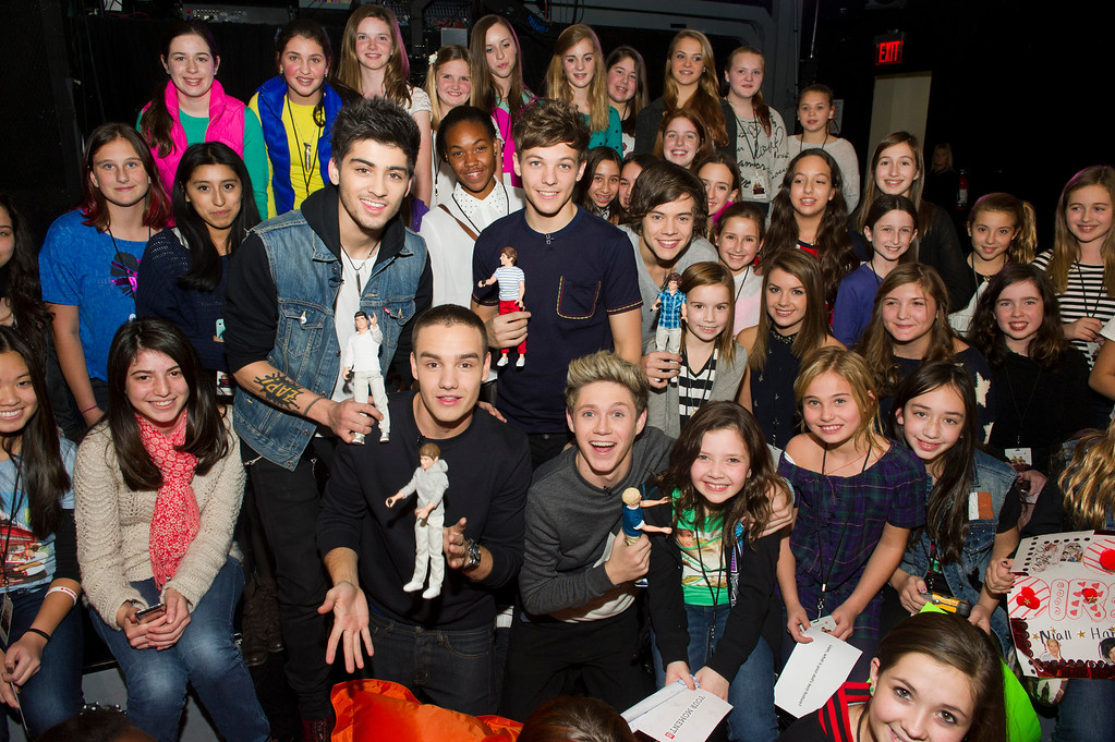 """. Worldwide musical sensation One Direction showcases their Hasbro dolls while greeting the winners of Nickelodeon\'s \""""Your Moment with 1D\"""" sweepstakes at an exclusive fan event on Monday, Nov. 26, 2012 in New York. (Photo by Charles Sykes/Invision for Hasbro/AP Images)"""