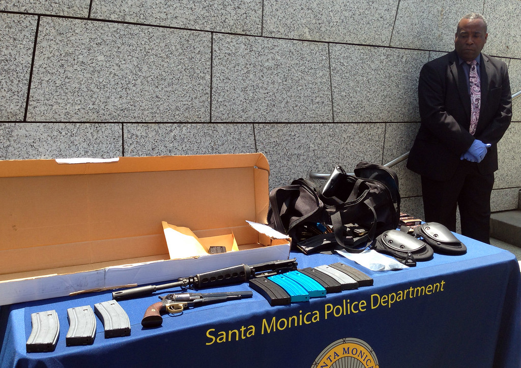 . An unidentified law enforcement official stands Saturday June 8, 2013, by weapons and other evidence recovered from the gunman in Friday\'s deadly shooting rampage that left four people dead, in Santa Monica, Calif. The gunman killed his father and brother at their home and another man at nearby Santa Monica College, authorities said. (AP Photo/Tami Abdollah)