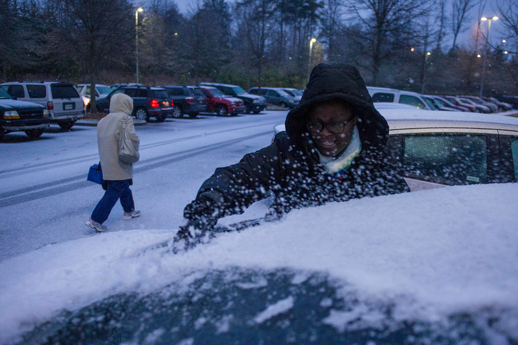 . Shmetrice Moore, a nurse at an Emory hospital,  scrapes snow and ice off her windshield as she and others are released early from their shift before a winter storm on Wednesday, Feb. 12, 2014, in Johns Creek, Ga.  From Texas to the Carolinas and the South\'s business hub in Atlanta, roads were slick with ice, tens of thousands were without power, and a wintry mix fell in many areas.  (AP Photo/John Amis)