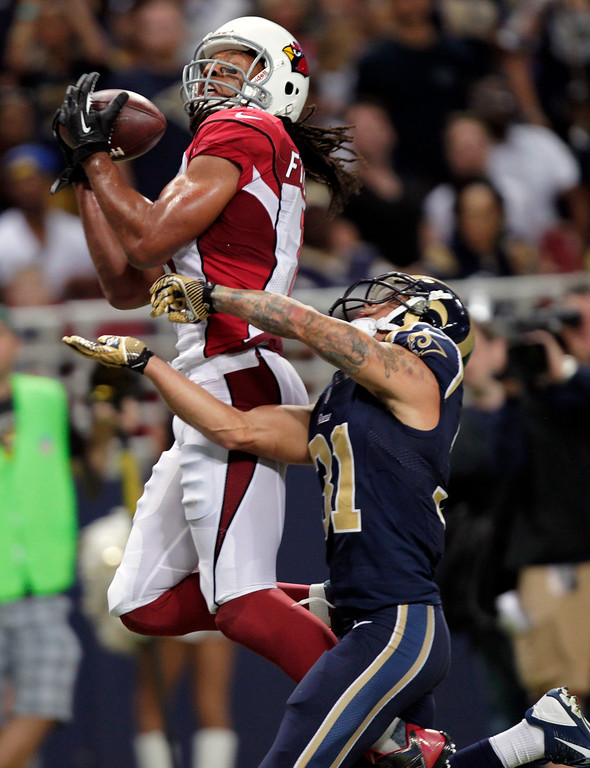 . Arizona Cardinals wide receiver Larry Fitzgerald, left, catches a 24-yard pass for a touchdown as St. Louis Rams cornerback Cortland Finnegan defends during the third quarter of an NFL football game on Sunday, Sept. 8, 2013, in St. Louis. (AP Photo/Tom Gannam)