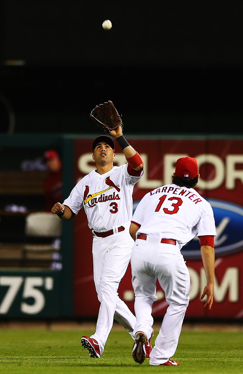 . Carlos Beltran #3 of the St. Louis Cardinals catches a pop fly as Matt Carpenter #13 looks on in the fifth inning against the Pittsburgh Pirates during Game Five of the National League Division Series at Busch Stadium on October 9, 2013 in St Louis, Missouri.  (Photo by Elsa/Getty Images)